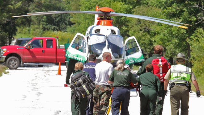 Emergency crews rush former FBI director Louis Freeh, 64, to a helicopter for transport to Dartmouth-Hitchcock Medical Center in Lebanon, N.H., following a crash Aug. 25 on Vermont 12 in Barnard.
