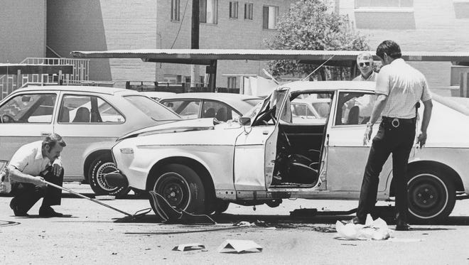 Investigators examine the car of Republic reporter Don Bolles, who was killed in 1976 when a bomb exploded.