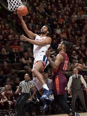 Virginia guard Braxton Key, left, drives past Virginia Tech defender Ahmed Hill, right, during the first half