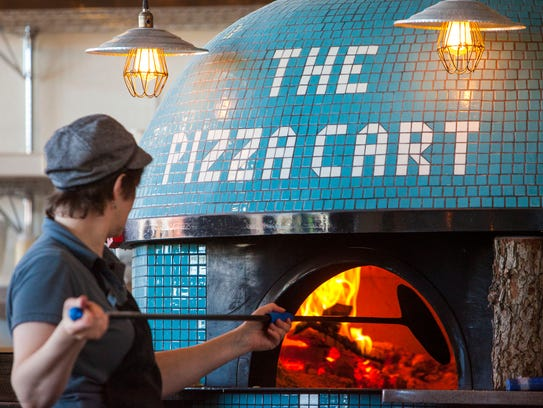 An employee puts a pizza in the oven at The Pizza Cart