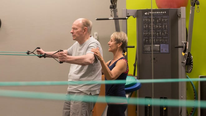 John Agel, 80, works out under the guidance of LouAnn Good at Good Life Works in south Fort Myers.  Agel lost his memory after having an aneurysm. For the past 18 months, he has regained it and doctors feel exercise he did before his health challenge played a major role in his recovery.