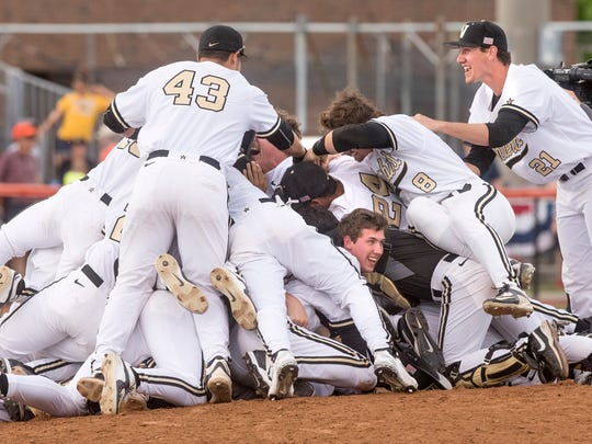 Vanderbilt's players pile on the pitcher's mound after winning their Super Regional game against Illinois in Champaign, Ill., on Monday.