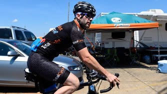 Jimmie Johnson (48) rides a bike in the infield of Talladega Superspeedway.
