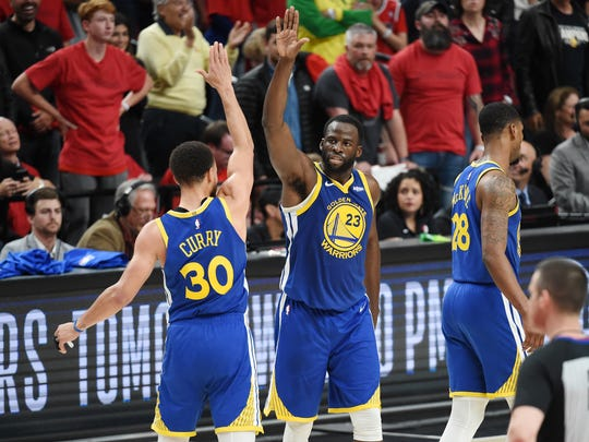 Stephen Curry high-fives Draymond Green during the second half against the Trail Blazers in Game 4 on May 20 in Portland.