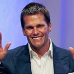 "New England Patriots quarterback Tom Brady gestures during an event at Salem State University in Salem, Mass., Thursday, May 7, 2015. An NFL investigation has found that New England Patriots employees likely deflated footballs and that quarterback Tom Brady was ""at least generally aware"" of the rules violations. The 243-page report released Wednesday, May 6, 2015, said league investigators found no evidence that coach Bill Belichick and team management knew of the practice. (AP Photo/Charles Krupa, Pool)"