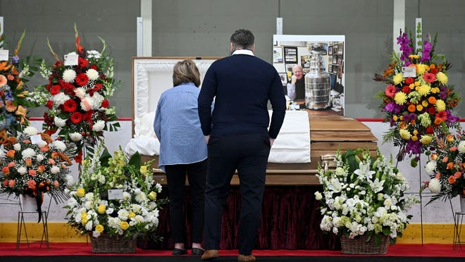 Mourners pay their respects at the casket of New England Sports Center general manager Wes Tuttle during a wake inside a NESC rink on Thursday.