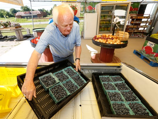 Eddie Wilkinson sets out a crate of blueberries before