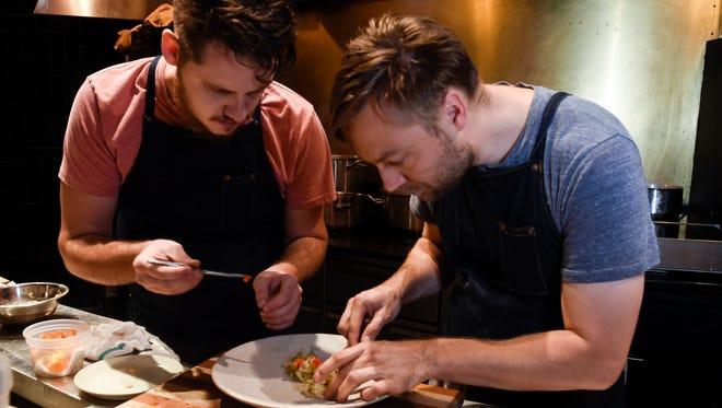 Chris Lewallen helps Chef Josh Habiger create a dish in the kitchen at Bastion.