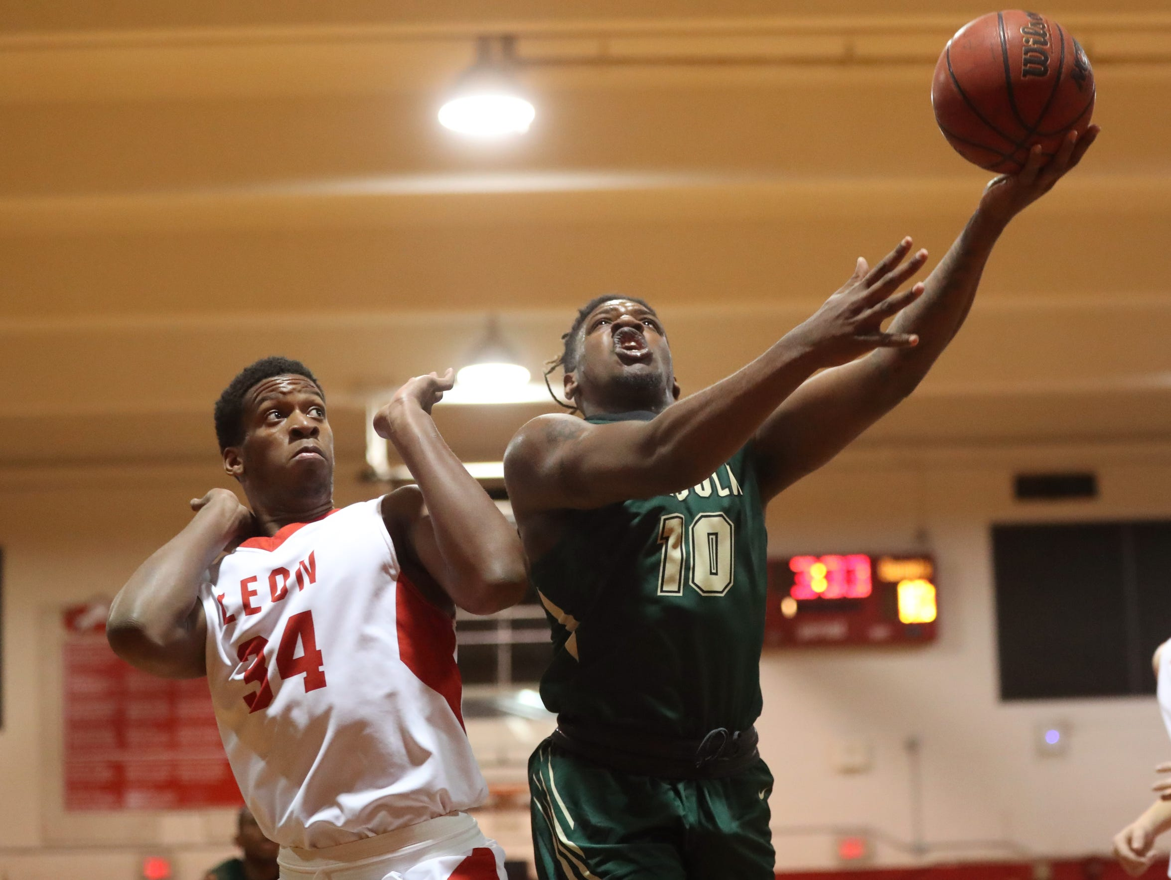 Lincoln's Tyler Farmer lays the ball up past Leon's