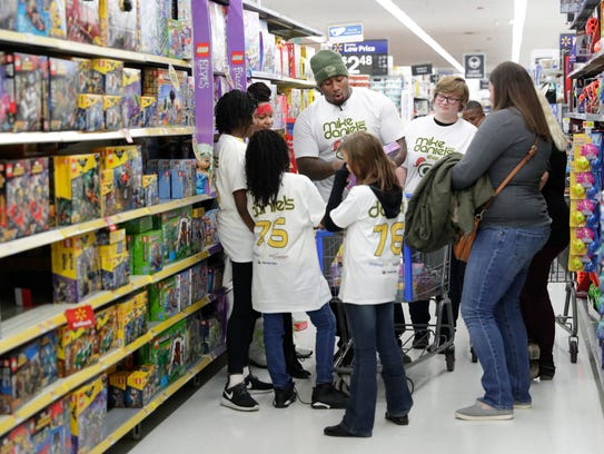 Green Bay Packers defensive tackle Mike Daniels exams Legos with Big Brothers Big Sisters shoppers during the Shop with a Jock event Monday, Dec. 11, 2017, at the Walmart on West Mason Street in Green Bay.