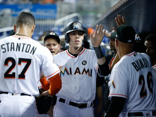 Miami Marlins' Christian Yelich, center, is congratulated by teammates after Yelich and Giancarlo Stanton (27) scored on a single by Justin Bour during the first inning of a baseball game against the New York Mets, Tuesday, June 27, 2017, in Miami. (AP Photo/Wilfredo Lee)