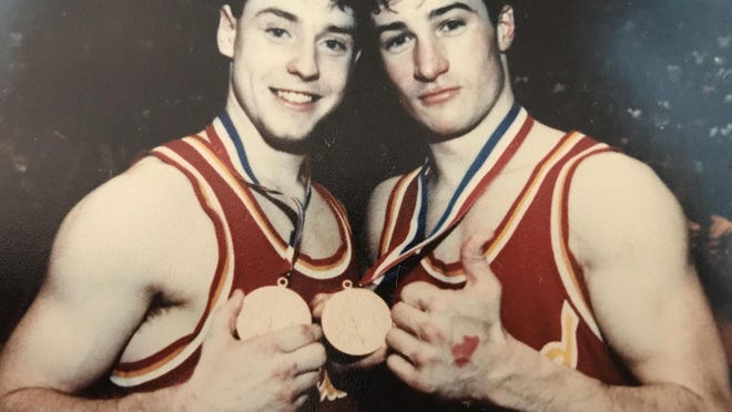 Girard basketball teammates John Mackanos and Brooks Bowen display their PIAA championship medals after the YellowJackets beat GAR Memorial 59-49 in 1990.