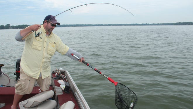 Chris Terry of Wauwatosa nets a smallmouth bass while fishing on Lac La Belle in Oconomowoc during the Aug. 21 solar eclipse.