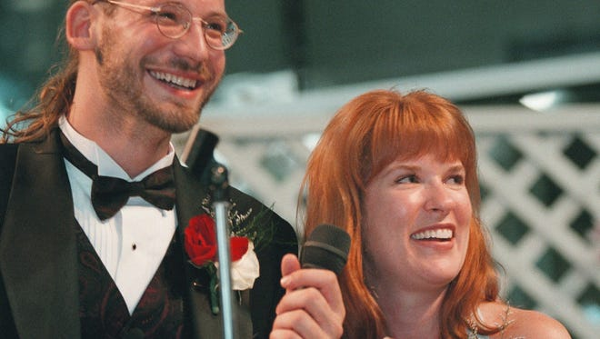 FILE - In this June 13, 1998 file photo, David Weinlick and Elizabeth Runze speak to the audience after Runze was picked to be Weinlick's bride at Mall of America in Bloomington, Minn. Weinlick's family and friends picked Runze from a group of 23 possible brides less than two hours before the wedding. The Minnesota couple who began their life together through an arranged marriage nearly 20 years ago are about to renew their vows. The ceremony on Friday, Aug. 18, 2017 will again be at the Mall of America. (AP Photo/Scott Cohen, File)