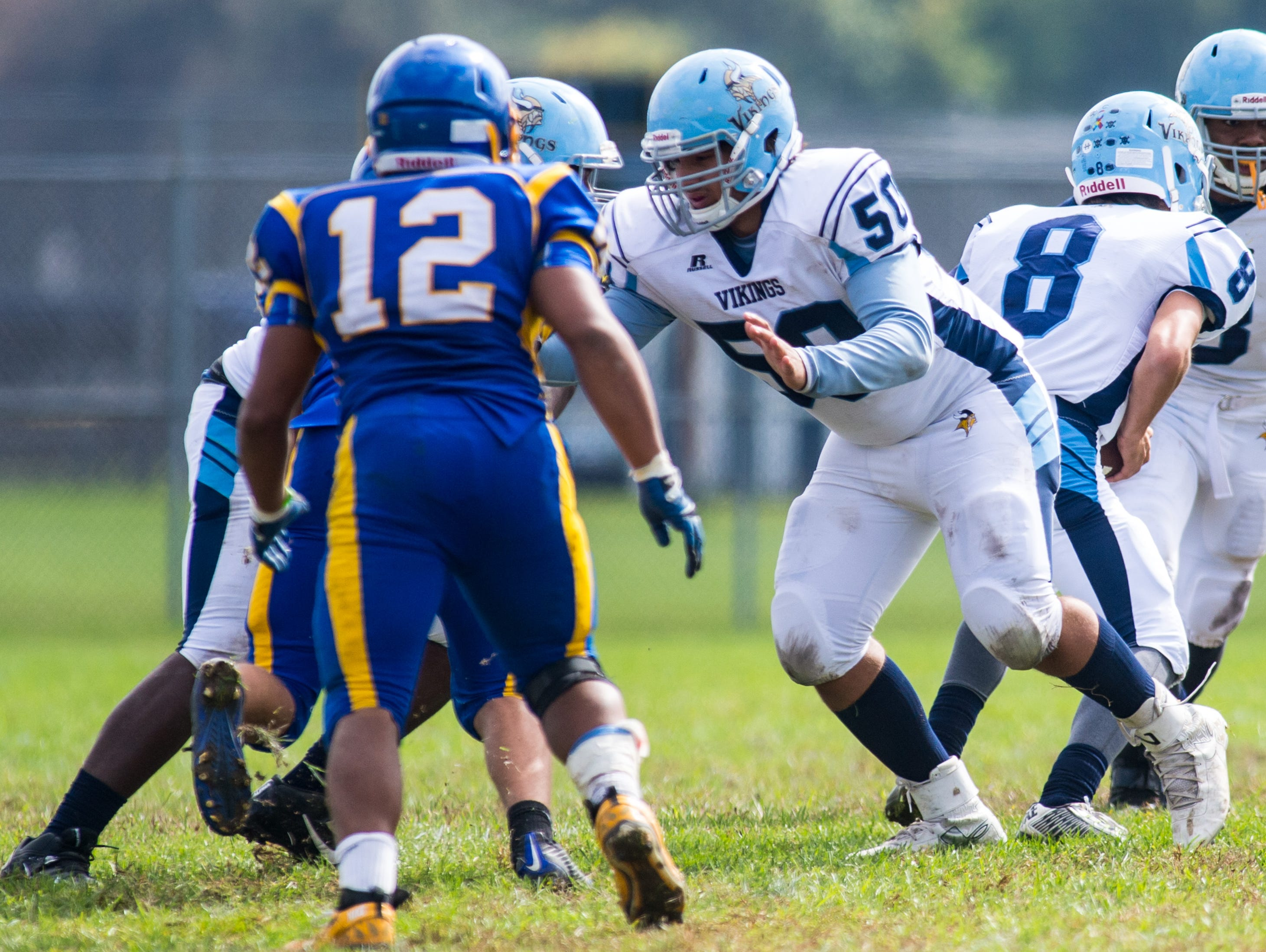 Cape Henlopen center Julian Medina (50) goes out for a block after snapping the ball to quarterback Dillon Adams (8) against Sussex Central in Georgetown on Saturday, October 10th.