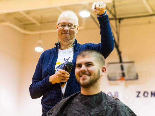 Pocomoke High girls basketball coach Gail Gladding shaves teacher Corey Zimmer's head during a pep rally as part of raising money for cancer research on Friday, December 18th