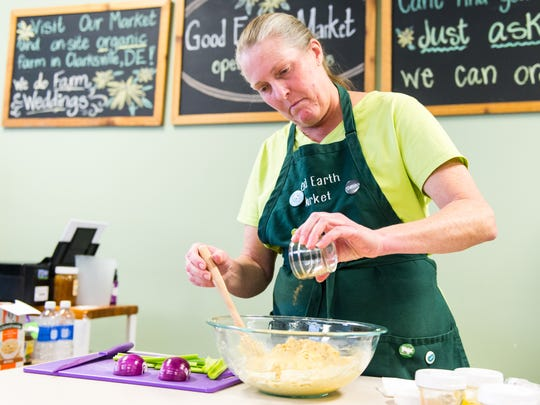 Lori Beinhauer of Good Earth Market in Rehoboth Beach mixes chickpea salad to show the ease of eating as a vegan on Tuesday, December 12.