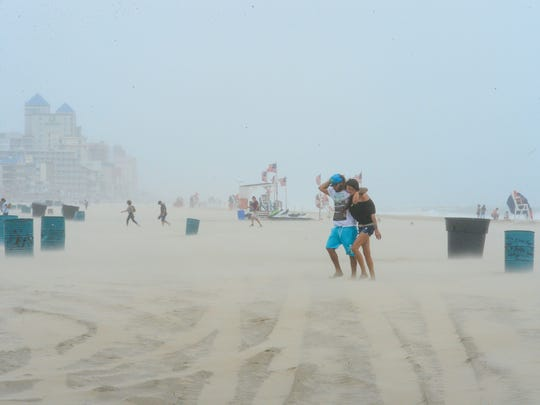 High winds from a summer nor'easter cause people to