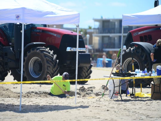 Ocean City Police and Forensics dig around the area where an unidentified body was found this morning around the 2nd Street beach in Ocean City on July 31.