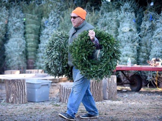 """Phil Civello, owner of Misty Run Tree Farm, carries some fresh wreaths for a customer purchasing greens. """"During Thanksgiving weekend we sold over 600 trees,"""" Civello said. He expects the next two weekends to be equally busy as people come to cut down their holiday tree."""
