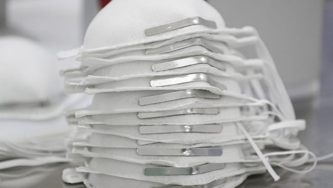 Face masks are stacked before getting technical information printed on them at a new factory in Mexico City, Thursday, May 21, 2020. An initiative by Mexico's National Autonomous University (UNAM) and Mexico City's government aims to fill the gap of the protective equipment desperately needed by doctors and nurses fighting the pandemic with this new factory to make N95 masks.