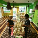 Salesman Floyd Hardrick, right, 24, of Detroit, assist Lisa Price, 55, of Detroit, on Friday, September 11, 2015, at 420 Dank, a medical dispensary, in Detroit. Price is suffering from Degenerative Disc Disease and has a medical licensed.