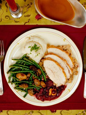 A plated Thanksgiving dinner with turkey, stuffing, mashed potatoes, green beans and cranberry sauce.