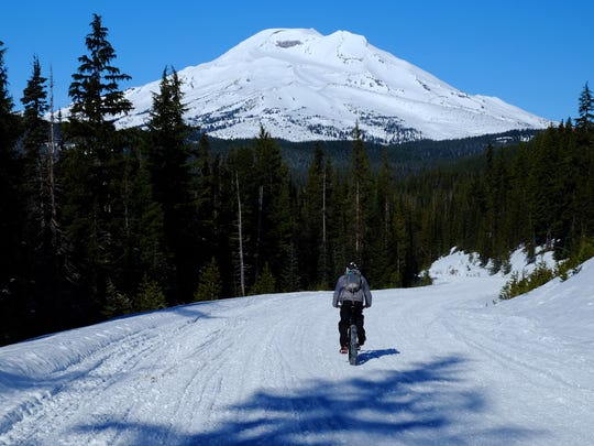 Zach Urness rides a fat bike down Cascade Lakes Highway (closed in winter) below South Sister.