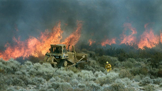 A bulldozer cuts a fire line in Nevada in this undated photo.
