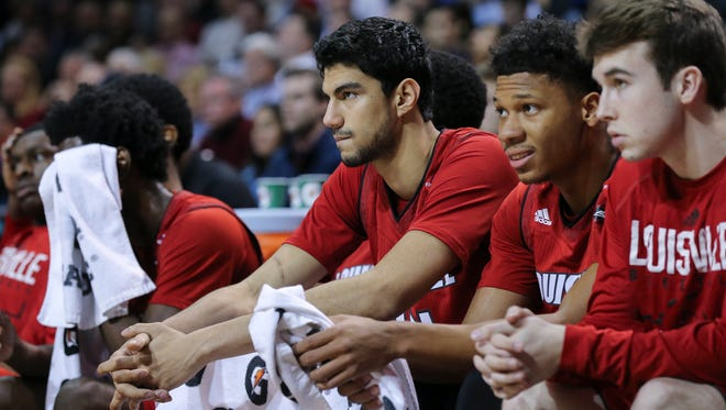 U of L's players Anas Mahmoud (14), center, and Dwayne Sutton (24) were somber as they watched the final seconds tick off during their loss to Virginia in the ACC Tournament in Brooklyn, NY.    Mar. 8, 2018