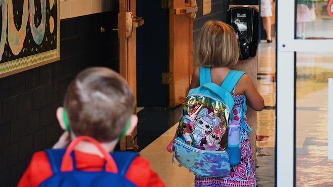 Children sanitize their hands as they arrive for class Friday at Chance Elementary School in Centralia.