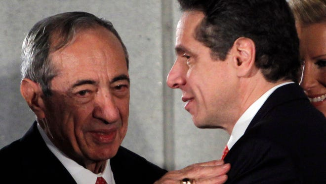In this Jan. 1, 2011 file photo, former New York Gov. Mario Cuomo, left, talks with his son and current New York Gov. Andrew Cuomo, during a swearing-in ceremony in the War Room at the Capitol in Albany.