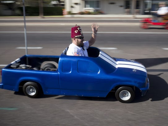A Shriner waves from his vehicle during Tempe's Veterans