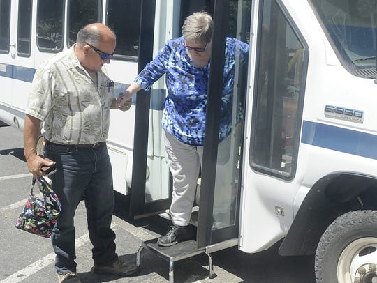 Driver Paul Silva helps Toni Dugan out of the van.