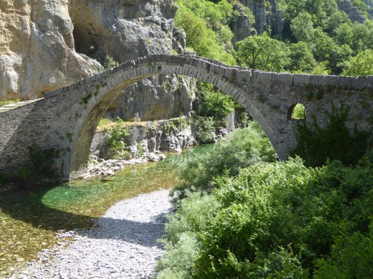 An ancient arched stone bridge still stands strong in Albania.
