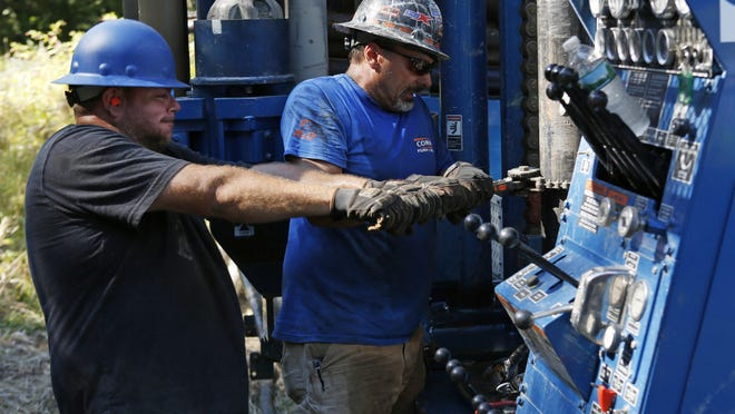 Josh Matthews, left, and Scott Costa pull on a wrench as they tighten a pipe during the drilling of a new well at a home, Thursday in Hampton Falls, N.H. Many private wells have gone dry amid this summer's prolonged drought and dry weather in the Northeast.