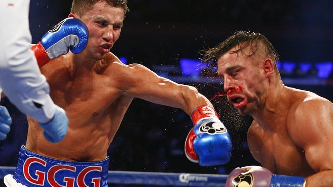 Gennady Golovkin, left, hits David Lemieux in the eighth round of a world middleweight title fight at Madison Square Garden. (AP Photo/Rich Schultz)