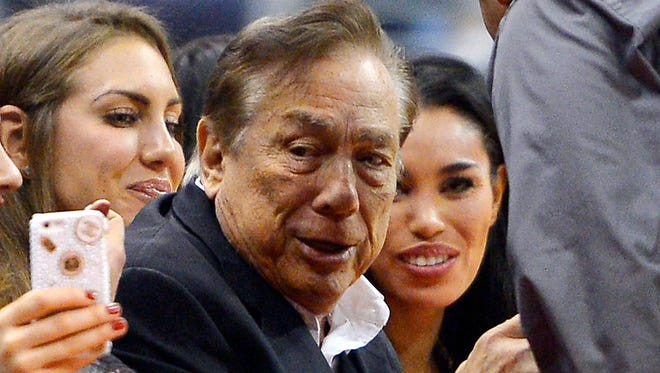Los Angeles Clippers owner Donald Sterling  and Vivian Stiviano watch the Clippers play in a 2013 game.