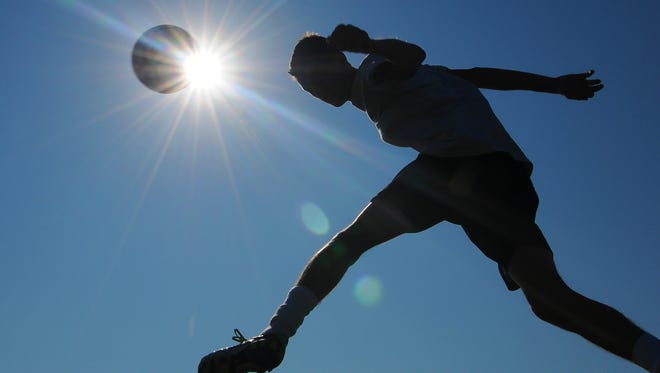 In this July 20, 2011 file photo, a member of the Salina South High School soccer team works out for conditioning training in Salina, Kansas. A new survey finds that being a good sport, positive coaching, and trying hard are key to kids having fun playing sports.