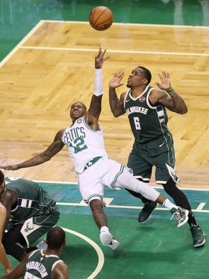 Terry Rozier of the Celtics throws up a wild shot while falling to the court with Eric Bledsoe of the Bucks guarding him during the second quarter.