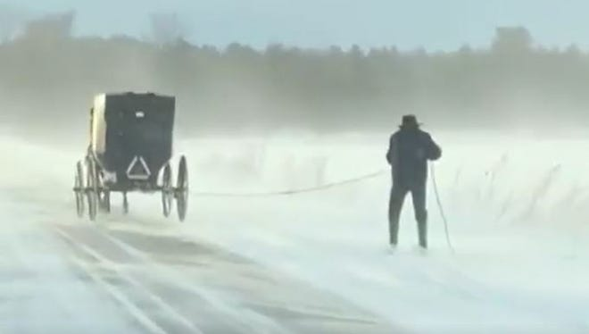 A man skis behind an Amish buggy in Morley, Mich.