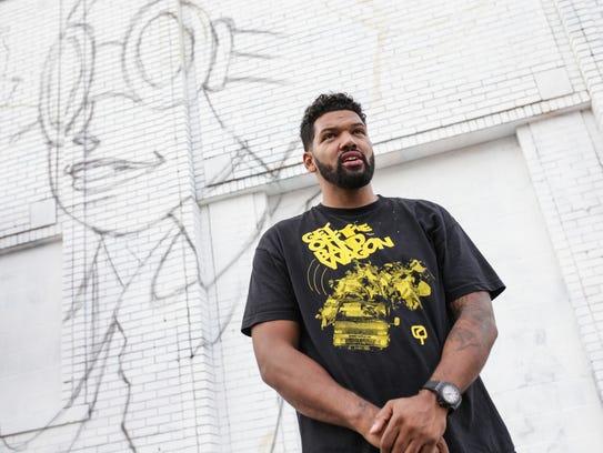 Artist Hebru Brantley stands by the start of his mural