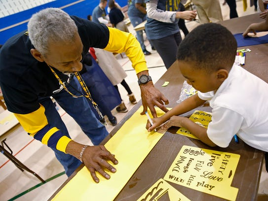 Former Indiana Pacer Darnell Hillman, left, helps Thomari