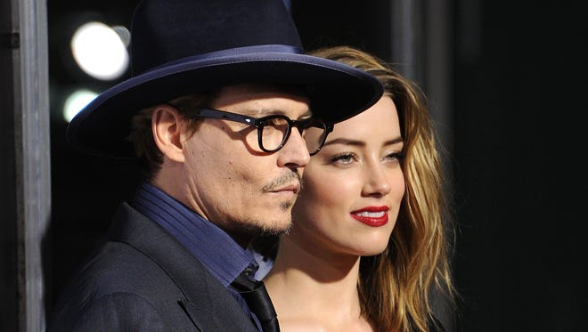 """Actor Johnny Depp and actress Amber Heard attend the US premiere of """"3 Days To Kill,"""" at Arclight Cinemas, February 12, 2014 in Hollywood, California."""