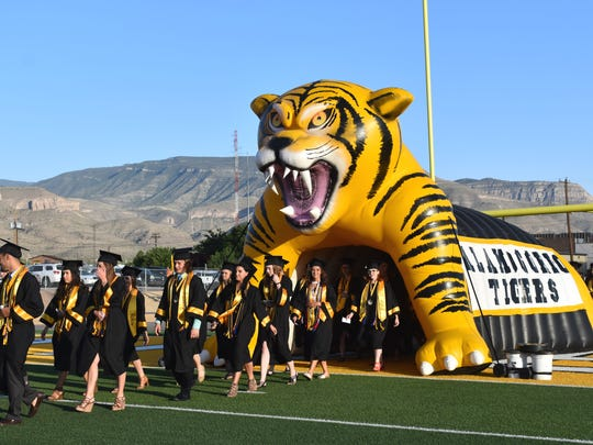 The AHS Class of 2017 make their way onto the football field during commencement Friday evening.