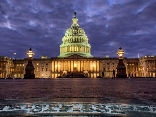In this Jan. 21, 2018, photo, lights shine inside the U.S. Capitol Building as night falls in Washington.