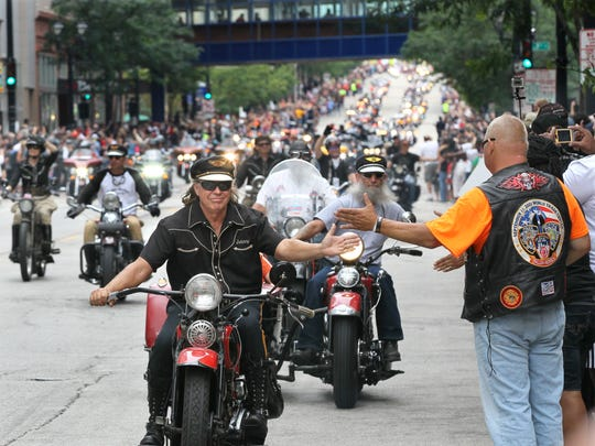 Riders slapped hands as they went past the parade watchers as they made their way down Wisconsin Ave. during the Harley-Davidson 110th Anniversary Parade on Aug. 31, 2013.