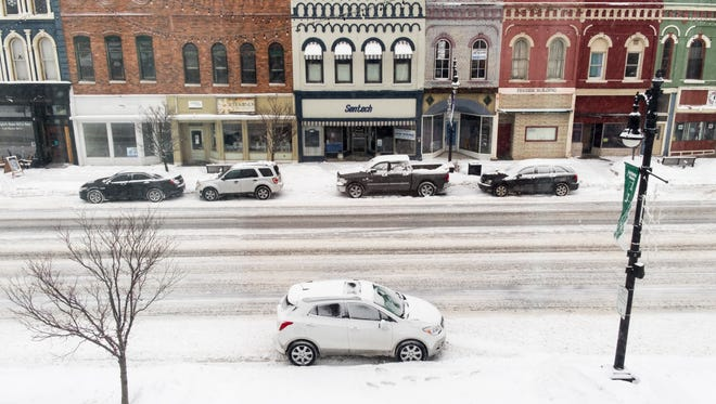 Snow begins to coat cars parked along Military Street in downtown Port Huron Feb. 9.