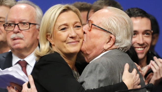"FILE - In this Sunday Nov. 30, 2014 file photo, French far-right Front National leader Marine Le Pen is kissed by her father Jean-Marie Le Pen after being re-elected as president of the party during the 15th congress of the party, in Lyon, central France. Marine Le Pen has launched an all-out offensive against her father, party founder Jean-Marie Le Pen, saying on Wednesday April 8, 2015, she will oppose his candidacy in upcoming elections and condemning as ""political suicide"" his repeated comments that the Nazi gas chambers were a ""detail in history.""  (AP Photo/Laurent Cipriani, File)"