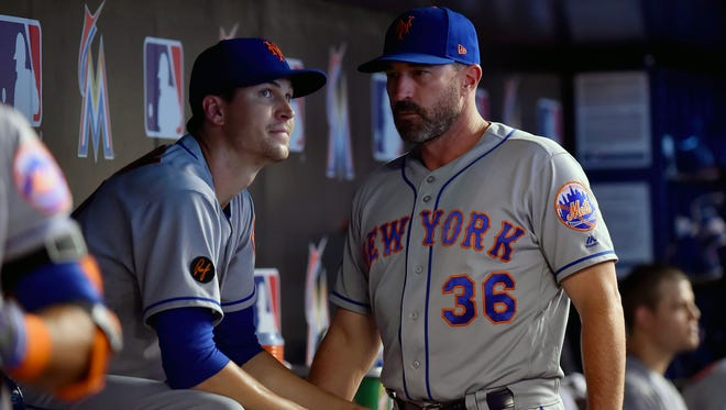 Jun 30, 2018; Miami, FL, USA; New York Mets manager Mickey Callaway (right) talks with Mets starting pitcher Jacob deGrom (left) in the dugout in the seventh inning against the Miami Marlins at Marlins Park.